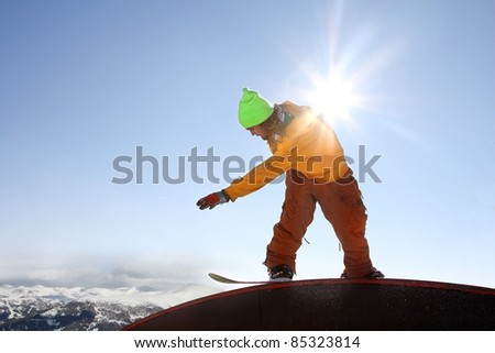 Cool snowboarder against blue sky - stock photo