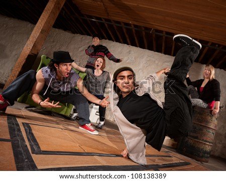 Cool South Asian teenager break dancing with friends - stock photo