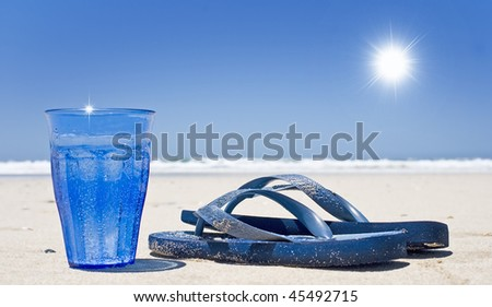 Cool sparkling water and beach sandals on the beach - stock photo