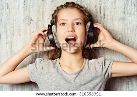 Cool teen girl enjoys the music in headphones. Studio shot. - stock photo