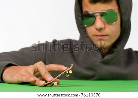 Cool teen posing with a tiny toy skateboard