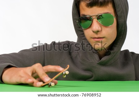 Cool teen posing with a tiny toy skateboard - stock photo