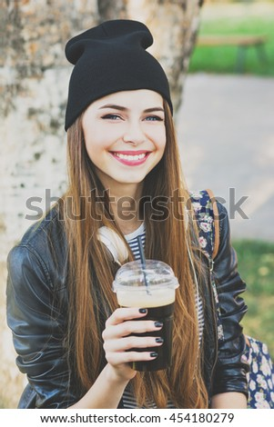 Cool teenage girl drinking coffee outdoors. Beautiful cheerful young woman in black leather jacket and black beanie hat drinking takeaway beverage in park. Closeup, matte filter applied. - stock photo