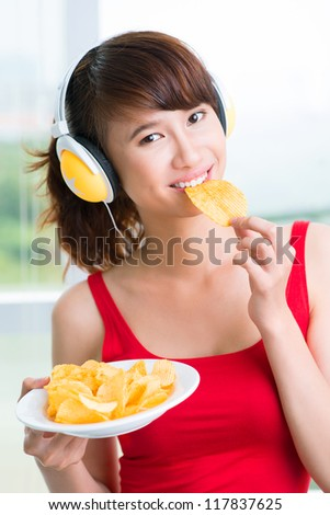 Cool teenage girl enjoying crisps listening to music - stock photo