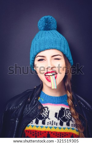 Cool teenage girl in colorful modern winter outfit with rainbow candy in her mouth. Trendy teenage model in blue hat eating colorful sweet food making facial expression. Black background, retouched. - stock photo