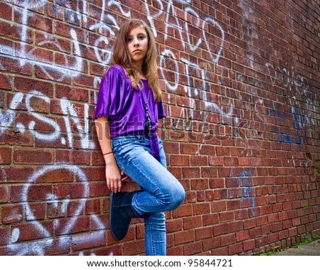 Cool teenage girl leaning casually against a graffiti covered urban wall - stock photo
