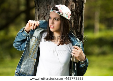 Cool teenage girl leaning on a tree in a park and listening to music on her headphones. She is wearing a denim jacket and baseball cap