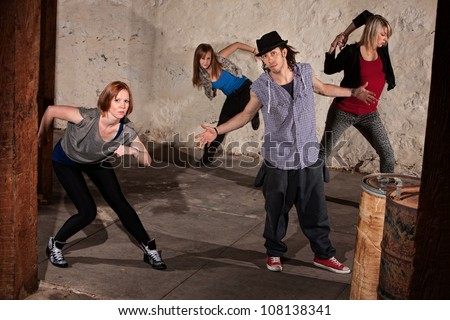 Cool urban dancers posing in underground setting - stock photo