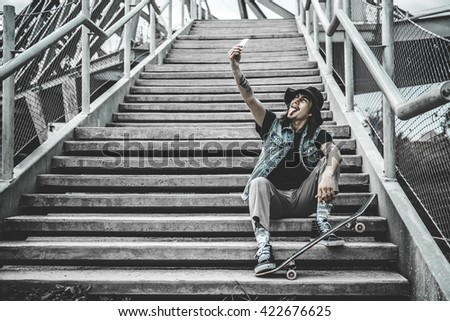 Cool urban skater guy at the stairs taking a self portrait with his smart phone - stock photo