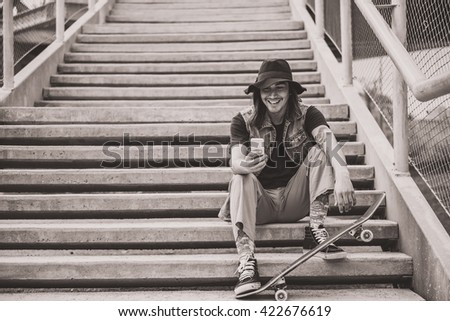 Cool urban skater guy at the stairs using his smart phone - stock photo