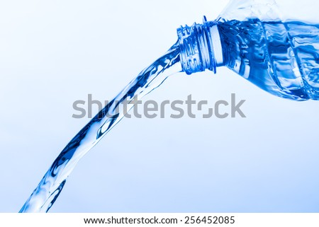 Cool Water Pouring from a Transparent Plastic Bottle, close up