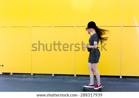 cool young and beautiful caucasian blonde teenager hipster skater girl with long gorgeous hair is posing smiling and having fun outside while skating with her cute little skate amazing summer day - stock photo