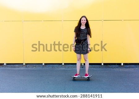 cool young and beautiful caucasian teenager hipster skater girl with long gorgeous hair is having fun outside while skating with her cute little skate during amazing summer day on a yellow background - stock photo