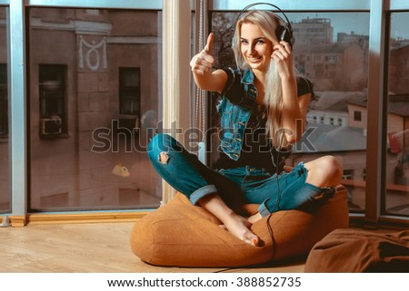 cool young blond woman listening to good music in headphones and shows class. Girl listening to the music. Blonde listen to the music in headphones. Music in headphones. - stock photo