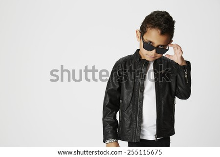 Cool young boy in sunglasses scrutinizing camera - stock photo