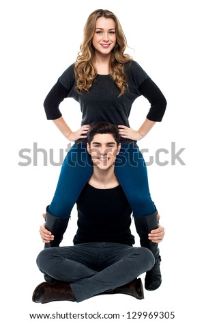 Cool young boy sitting on the floor with girlfriend on his shoulders. - stock photo
