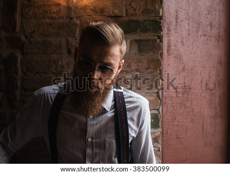 Cool young businessman with beard and eyeglasses