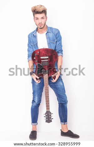 cool young guitarist showing his red electric guitar on white background - stock photo