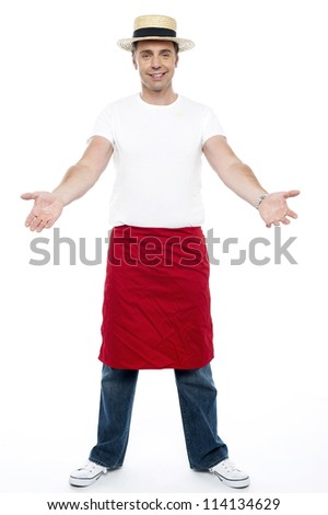 Cool young guy welcoming you. Wearing hat and apron tied on his waist