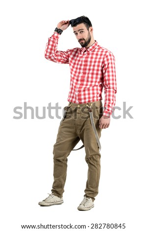 Cool young handsome hipster with flirting look putting sunglasses on his head. Full body length portrait isolated over white background.  - stock photo