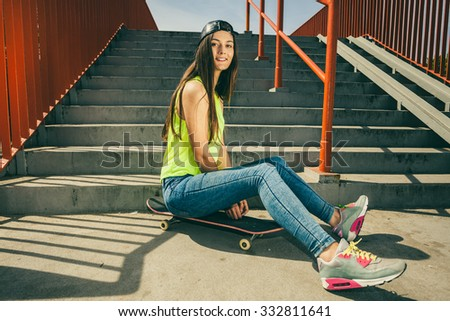 Cool young long haired girl sitting on skateboard near the urban stairs. Active lifestyle funky in summer. Trendy sport teen. - stock photo