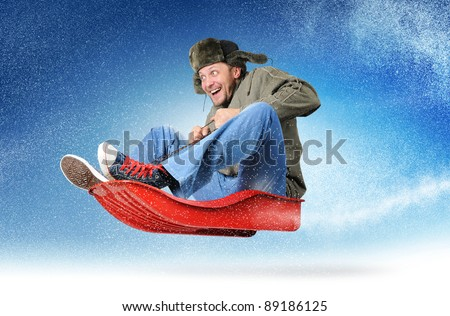 Cool young man fly on a sled in the snow, concept winter driving