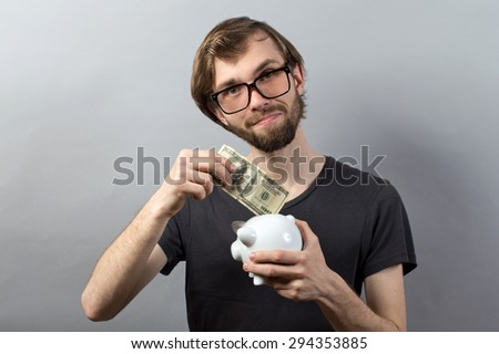 Cool young men with a money box on a grey background - stock photo