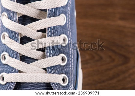 cool youth blue gym shoes with white laces  on brown parquet  wooden floor with copy place   - stock photo