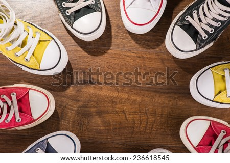 cool youth white yellow red blue black  gym shoes standing in circle  on brown parquet  wooden floor with copy place  top view  - stock photo