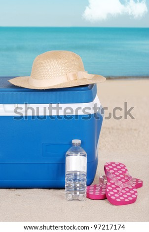 cooler woman hat and sandals on the beach - stock photo