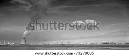 cooling towers of a nuclear power plant creating clouds in the Antwerp harbor - stock photo
