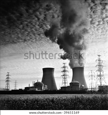 cooling towers of a nuclear power plant creating dark clouds monochrome film grain - stock photo