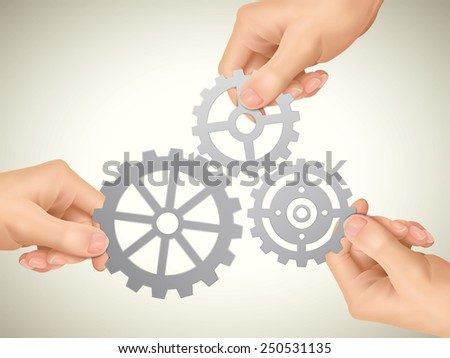 cooperation concept: hands holding gears over beige background - stock photo