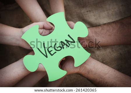 Cooperation - Jigsaw Puzzles in Teams Hands spelling out vegan - stock photo