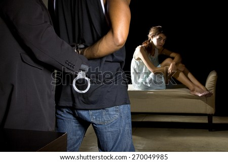 Cop arresting a man for domestic violence and female victim in the background.  She is sitting in the dark and looks afraid. - stock photo