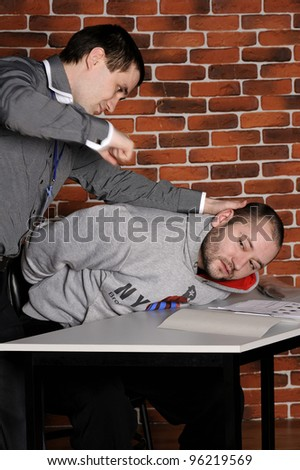 Cop beats handcuffed suspect against a break wall - stock photo