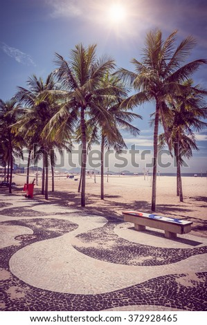 Copacabana with palms and mosaic of sidewalk in Rio de Janeiro. Brazil - stock photo