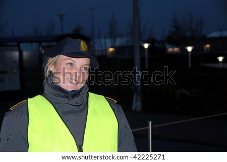 COPENHAGEN – DEC 5: A policewoman smiles while standing at the main gate at the Bella Center outside the UN Climate Change Conference on December 5, 2009 in Copenhagen. - stock photo