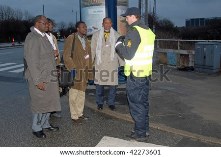 COPENHAGEN - DEC 5: Delegates from Niger talk to a policeman at a security checkpoint at the UN Climate Change Conference on December 5, 2009 in Copenhagen. - stock photo