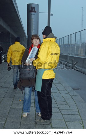 COPENHAGEN - DEC 7: Opening Day: Greenpeace activist talk to a woman near the entrance to the Bella Center at the UN Climate Change Conference on December 7, 2009 in Copenhagen, Denmark. - stock photo