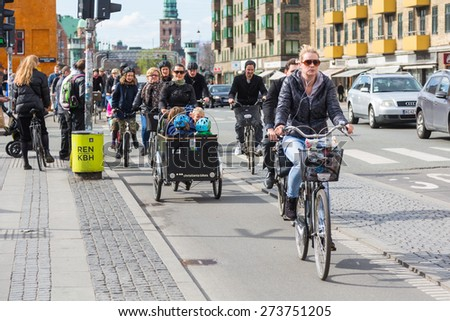 COPENHAGEN, DENMARK - APRIL 28, 2015: People going by bike in the city. A lot of commuters, students and tourists prefer using bike instead of car or bus to move around the city. - stock photo