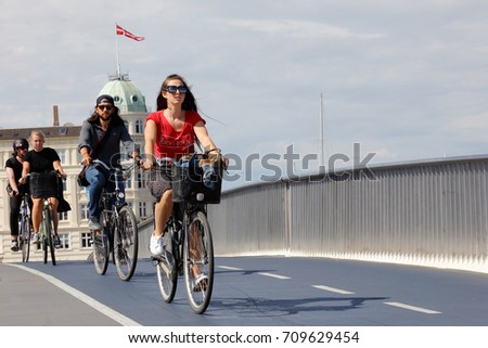 Copenhagen, Denmark - August 24, 2017: A group of three cyclists cycles over the bridge Inderhavnbroen.