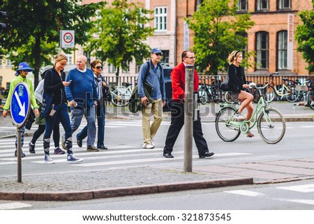 COPENHAGEN, DENMARK - AUGUST 01, 2015: People going by bike in the city. A lot of commuters, students and tourists prefer using bike instead of car or bus to move around the city. - stock photo