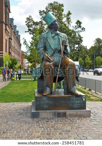 COPENHAGEN, DENMARK - AUGUST 22, 2014:  Statue of Hans Christian Andersen looking across Boulevard to Tivoli Gardens in Copenhagen, Denmark.  Statue made by sculptor Henry Luckow-Nielsen in 1961. - stock photo