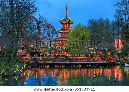 COPENHAGEN, DENMARK - DECEMBER 14, 2015: Evening view of Tivoli Gardens with Chinese pagoda on the shore of pond and Daemonen roller coaster. Tivoli is the most-visited theme park in Scandinavia. - stock photo