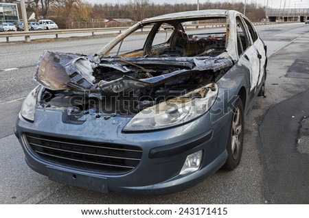 COPENHAGEN, DENMARK - JANUARY 11, 2015: A Peugeot car destroyed by fire after an accident. It was left outside a Peugeot dealer by the towing Company. Nobody was injured at the accident.  - stock photo