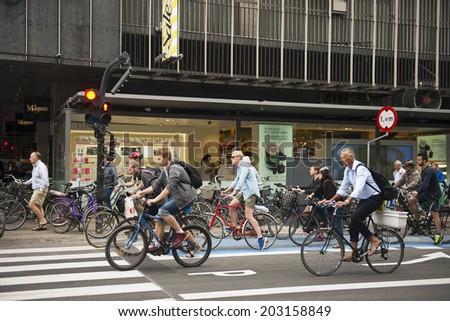 COPENHAGEN, DENMARK - JULY 2: Many people biking in centre of city on July 2, 2014 in Copenhagen - stock photo