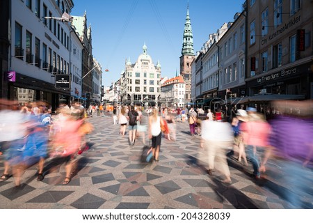 COPENHAGEN, DENMARK - JULY 9, 2014: Tourists and local citizens stroll through the central pedestrian area of the Danish capital of Copenhagen as local restaurants and merchants prepare for tourists. - stock photo