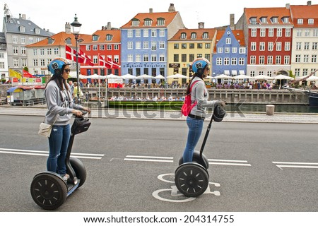 COPENHAGEN, DENMARK - JULY 2: Tourists riding segways in Nyhavn on July 2, 2014 in Copenhagen - stock photo