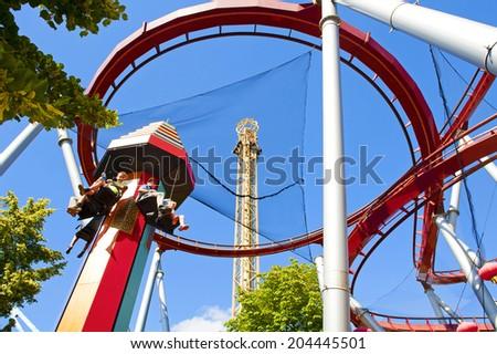 COPENHAGEN, DENMARK - JUNE 30: Demon Roller Coaster, Golden Tower and Temple Tower in Tivoli on June 30, 2014 in Copenhagen - stock photo
